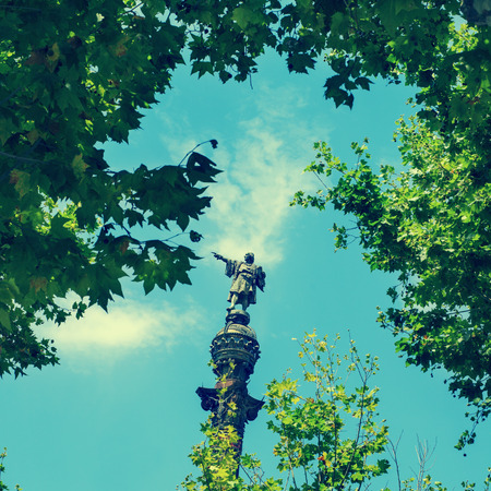 wanderlust: a view of the Columbus Monument in Barcelona, Spain, between some trees, with a retro effect