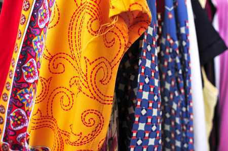 used clothes: closeup of some used clothes hanging on a rack in a flea market Stock Photo