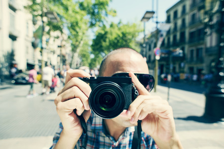 observer: a young caucasian man wearing sunglasses points his camera to the observer at La Rambla in Barcelona, Spain
