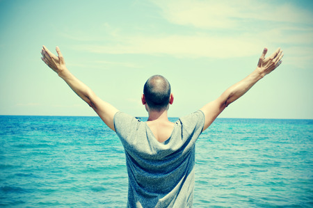 arm: closeup of a young caucasian man seen from behind with his arms in the air in front of the ocean, feeling free, with a slight vignette added