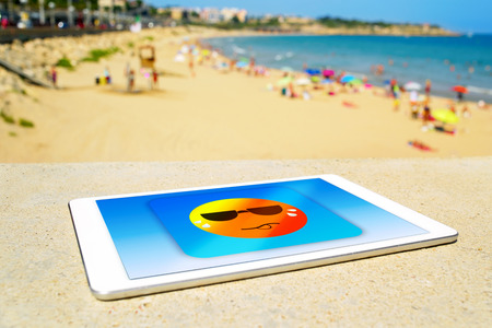 vac: a tablet computer with an icon of a sun wearing sunglasses and sweating, designed by myself, at the beach, depicting the concept of heat or heat wave