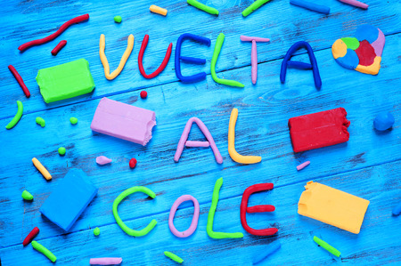 cole: the sentence vuelta al cole, back to school in spanish, written with modelling clay of different colors, on a blue rustic wooden background