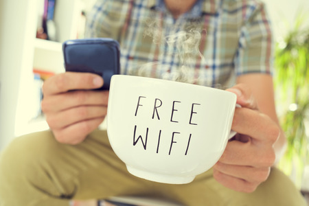 gros plan d'un jeune homme caucasien utilisant un smartphone avec une tasse de café ou de thé avec le wifi gratuit de texte écrit en elle