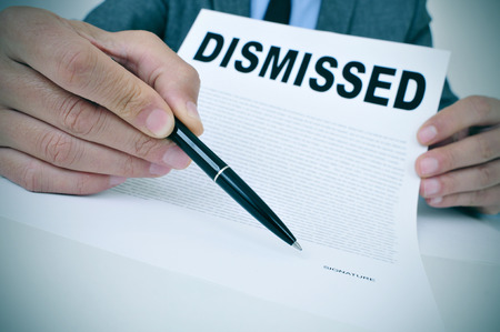 dismissal: a young businessman sitting at his office desk shows a document with the word dismissed written in it and points with a pen where to sign