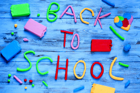modelling clay: the sentence back to school written with modelling clay of different colors on a blue rustic wooden background Stock Photo