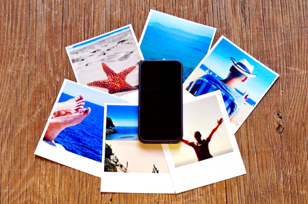 vac: high-angle shot of a smartphone and some photos, shot by myself, of a young man in the beach and some other beach scenes, placed on a rustic wooden table