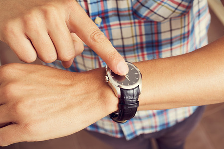 llegar tarde: primer plano de un hombre caucásico joven tocando el dedo índice en su reloj de pulsera