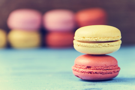 cross processed: some appetizing macarons with different colors and flavors on a blue rustic wooden surface, cross processed