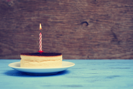 lighted: a cheesecake with a lighted birthday candle on a rustic blue wooden surface, with a retro effect Stock Photo