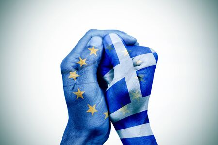 creditors: hand patterned with the flag of the European Community envelops another hand patterned with the flag of Greece Stock Photo