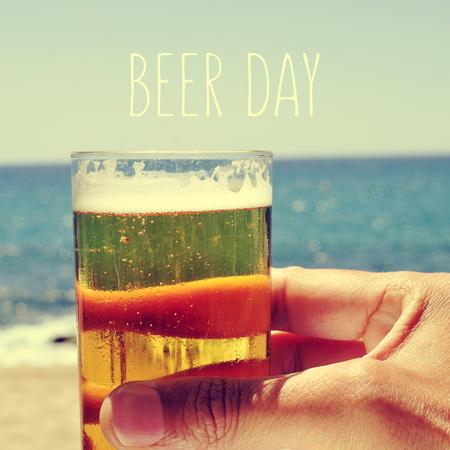 cerveza: Primer plano de la mano de un hombre con una cerveza refrehing cerca del mar y el día de la cerveza de texto