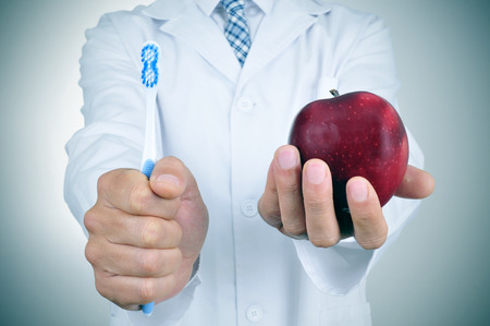 blue plaque: a dentist showing a toothbrush and an apple depicting the importance of tooth brushing and eating apples for a good dental health