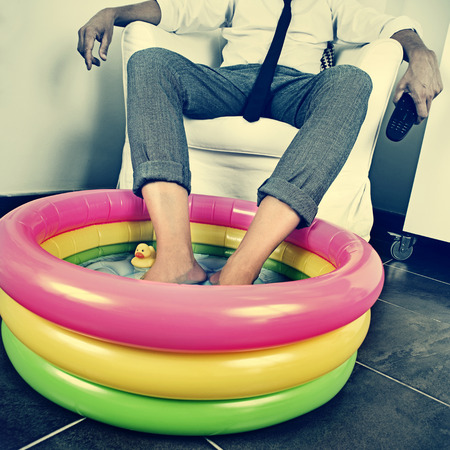 a young man in suit soaking his feet in an inflatable water pool indoors, with a dramatic effect, depicting the concept of staying at home on vacation