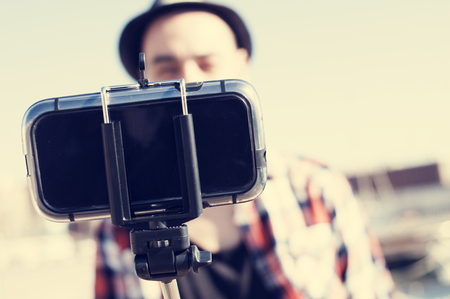 causasian: a young causasian man wearing a plaid shirt and a hat takes a self-portrait with a selfie stick outdoors