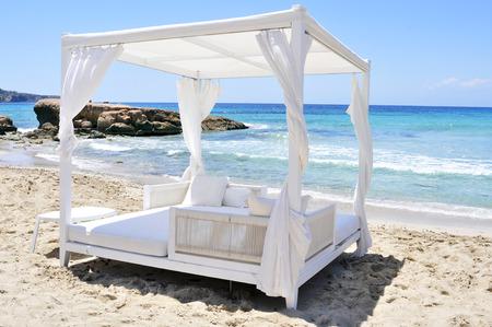 cama: detalle de una cama blanca en un club de playa en una playa de arena blanca en Ibiza, España Foto de archivo