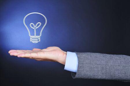 schöpfung: Nahaufnahme von einem Mann in einem Anzug mit einer Illustration einer Glühbirne in der flachen Hand