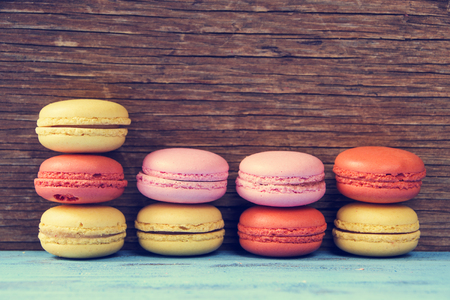 processed: some appetizing macarons with different colors and flavors on a blue rustic wooden surface, cross processed
