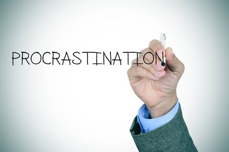 delaying: closeup of the hand of a man writing the word procrastination in the foreground Stock Photo