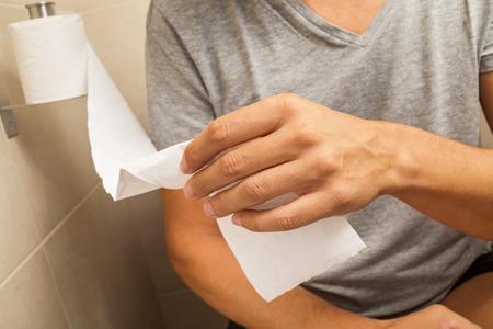 diarrea: detalle de un hombre caucásico joven en el inodoro conseguir un poco de papel del rollo