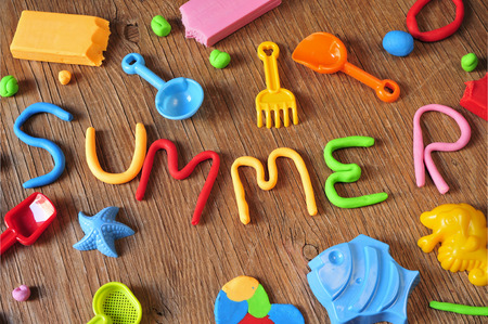 modelling clay: the word summer made from modelling clay of different colors and some beach toys such as toy shovels and sand moulds, on a rustic wooden surface