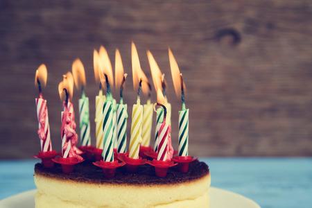 tortas cumpleaÑos: primer plano de un pastel de queso con algunas velas de cumpleaños encendidas de diferentes colores, con un efecto retro