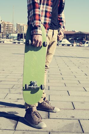 swagger: young caucasian man wearing a plaid shirt holds a green skateboard in his hand Stock Photo