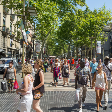 rambla: Barcelona, Spain - July 10, 2015: A crowd in La Rambla in Barcelona, Spain. Thousands of people walk daily by this popular pedestrian mall 1.2 kilometer-long