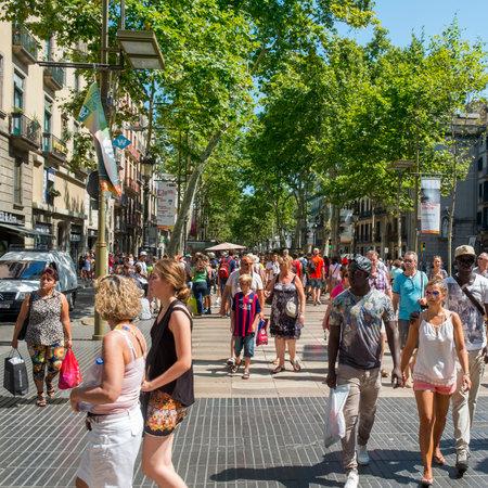 barcelone: Barcelone, Espagne - 10 Juillet, 2015: Une foule à La Rambla à Barcelone, Espagne. Des milliers de personnes marchent quotidiennement par cette rue piétonne populaire 1,2 km de long Éditoriale