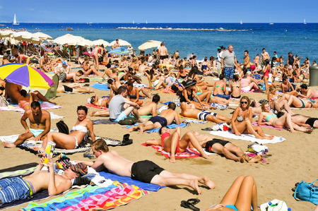 beach front: Barcelona, Spain - August 19, 2014: A crowd of bathers in La Barceloneta Beach in Barcelona, Spain. This popular beach hosts about 500000 visitors from everywhere during the summer season Editorial