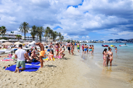 den: Ibiza Town, Spain - June 16, 2015: Sunbathers in the popular Platja den Bossa beach in Ibiza Town, Spain. Ibiza is a well-known summer tourist destination in Europe