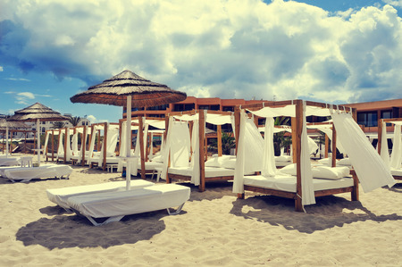 detail of some beds and sunloungers in a beach club in a white sand beach in Ibiza, Spain Stock Photo