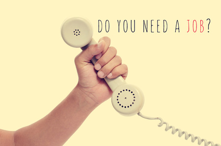 joblessness: man holding the handset of a telephone and the text do you need a job? with a retro effect Stock Photo
