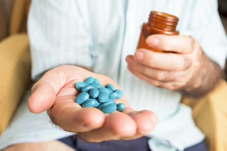 closeup of an old caucasian man with a pile of blue pills in his hand