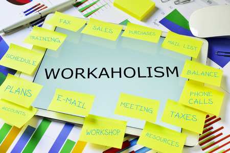 work addicted: the text workaholism in a tablet computer full of sticky notes with different tasks,  placed on an office desk full of charts