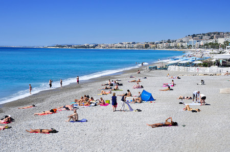 bordering: Nice, France - May 16, 2015: People sunbathing on the beach in Nice, France. The long and famous seafront of Nice bordering the Mediterranean Sea is known as the Promenade des Anglais