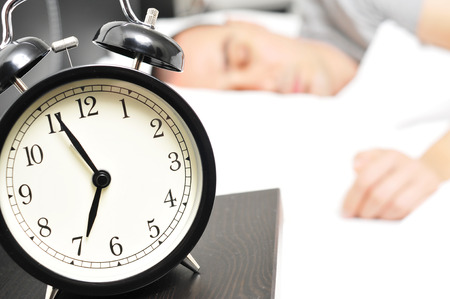 night table: closeup of an alarm clock at 6.55 in the morning on the night table and a young caucasian man sleeping in bed