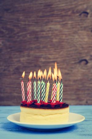 torta candeline: primo piano di una cheesecake con alcune candele accese compleanno di colori diversi, con un effetto retr�