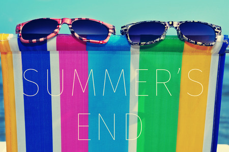 a pair of sunglasses on a colorful deck chair and the text summers end Stock Photo
