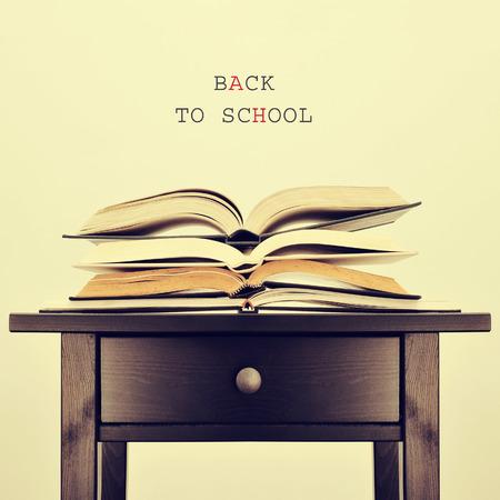 libros abiertos: algunos libros abiertos sobre una mesa y la pena volver a la escuela en un fondo de color beige, con un efecto retro Foto de archivo