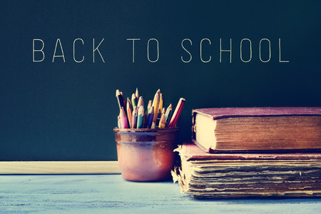 secondary schools: some pencils in a pot, some old books on a blue school desk, and the text back to school written on a chalkboard, with a filter effect Stock Photo