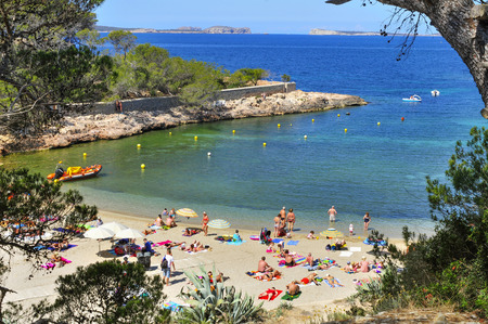 San Antonio, Spain - June 18, 2015: Sunbathers at Cala Gracio beach in San Antonio, in Ibiza Island, Spain. Ibiza is a well-known summer tourist destination in Europe Редакционное