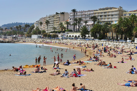 promenade: Cannes, France - May 14, 2015: Sunbathers at the public beach at the end of the Promenade de la Croisette in Cannes, France. This promenade is famous because of the Cannes Film Festival Editorial