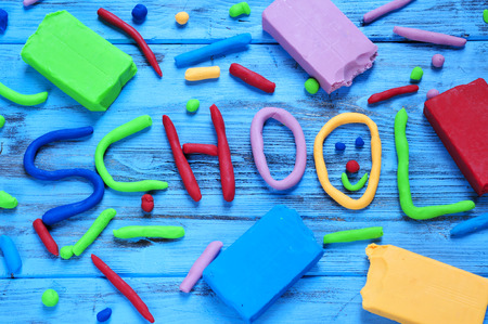 modelling clay: the word school written with modelling clay of different colors on a blue rustic wooden background