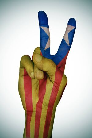 separatist: the hand of a young man giving the V sign patterned with the Estelada, the Catalan pro-independence flag