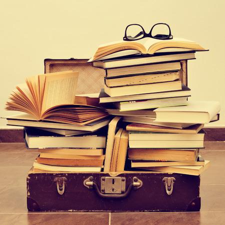 maleta: un par de anteojos en una pila de libros colocados en una maleta vieja, con un efecto retro