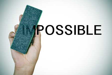 deleting: closeup of the hand of a young man deleting the word impossible with an eraser Stock Photo