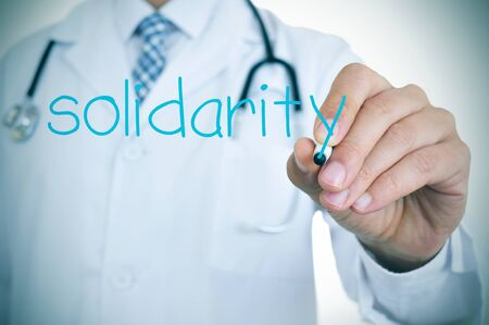 geriatrician: closeup of a young doctor writing the word solidarity in the foreground, for the concept of medical solidarity and aid