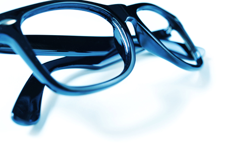 closeup of a pair of black plastic-rimmed eyeglasses on a white surface