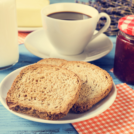 comiendo pan: primer plano de unas tostadas en un plato, una taza de caf�, una botella con leche y un tarro de mermelada sobre una mesa de madera azul r�stico, con un efecto de procesos cruzados Foto de archivo