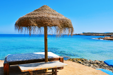 beaches of spain: detail of a relaxing area in a Cala Conta beach in Ibiza Island, Spain, with a comfortable sunlounger and a rustic umbrella made of natural fibers